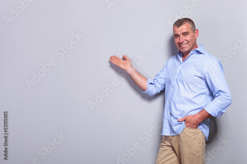casual old man presents with hand in pocket