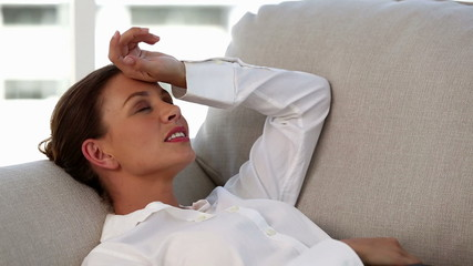 Attractive businesswoman having a nap to stop her headache