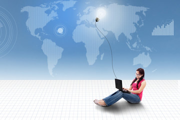 Asian female using laptop with lightbulb on world map background