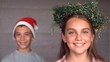 Siblings wearing garland and hat to celebrate christmas