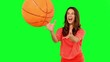 Smiling woman catching a basket ball on green screen