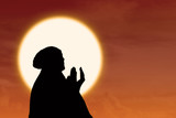 Silhouette of female muslim pray at sunset