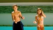 Siblings dancing together in front of the swimming pool