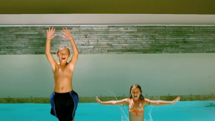 Brother and sister jumping backwards into pool