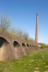 Ancient brick factory with brick kiln holes and chimney