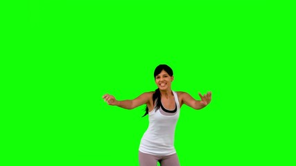 Woman in sportswear leaping on green screen