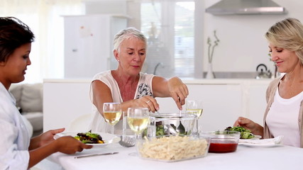 Mature woman offering meal to her friends