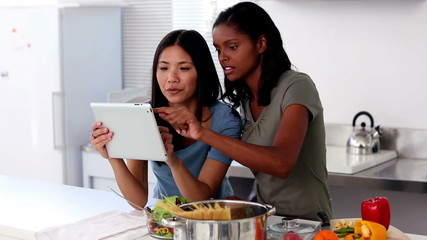 Young women following online recipe on a tablet pc