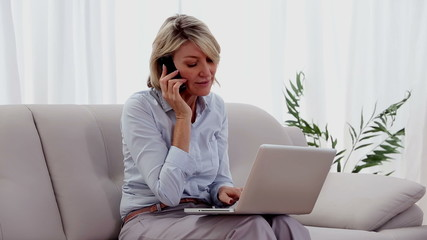 Woman on the phone using laptop