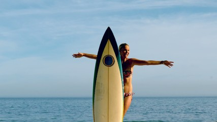 Female surfer jumping out from behind her board