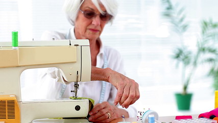 Retired woman using the sewing machine