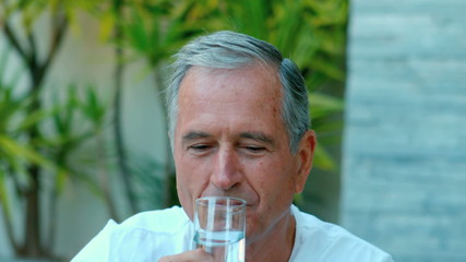 Retired man drinking water outside
