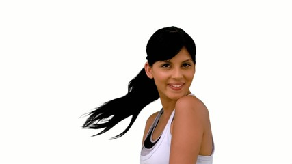 Fit woman tossing her hair and smiling at camera