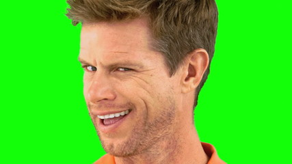 Cheerful man winking an eye on green screen