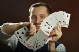 Happy skillful male magician performing playing cards jugglery