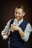 Magician juggling with playing cards while winking at the camera