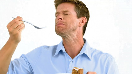 Man savouring a delicious cake on white background