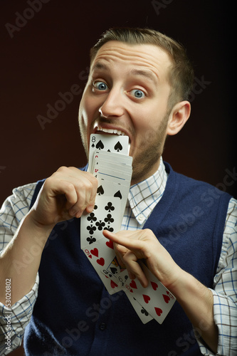 Funny male magician pulling playing cards out of his mouth