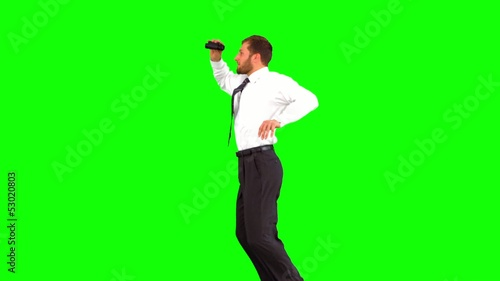 Businessman looking through binoculars while jumping