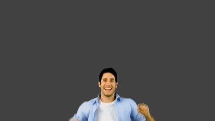 Man jumping for joy on grey background