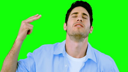 Man pretending to shoot himself with hand on green screen