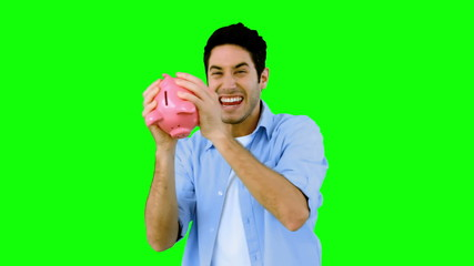 Man shaking piggy bank excitedly on green screen