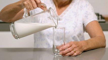 Woman pouring glass of milk in the kitchen