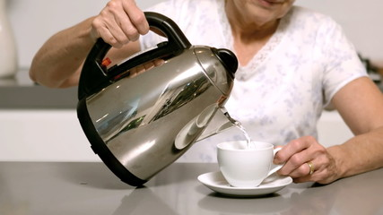 Woman pouring hot water from kettle into cup
