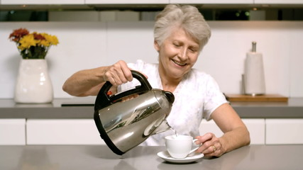 Elderly woman pouring boiling water from kettle into cup