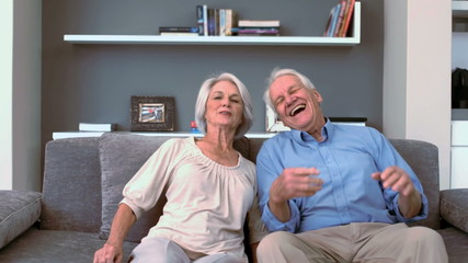 Retired couple flopping down on the couch