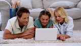 Parents and daughter using laptop on floor