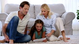 Parents and daughter using tablet on floor