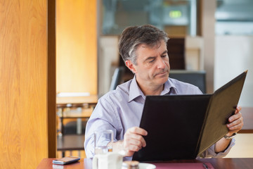 Man in a coffee shop looking at the menu