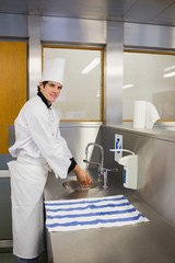 Smiling chef washing hands