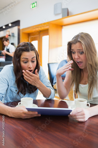 Women looking surprised while holding a tablet