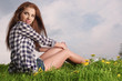 young beautiful brunette woman sitting on grass