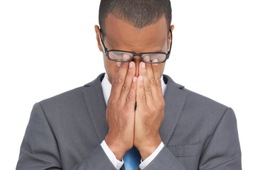 Businessman with glasses holding his head between hands