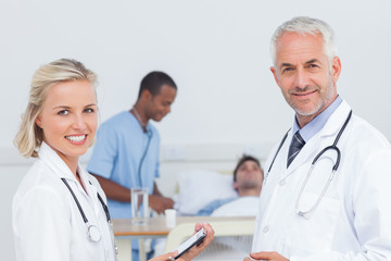 Smiling doctors standing in front of patient