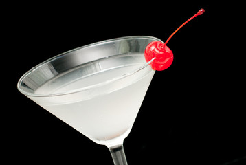 cocktail in martini glass witj red cherry closeup