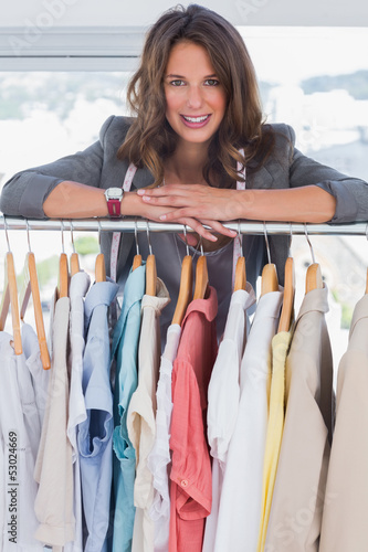 Smiling fashion designer leaning on clothes