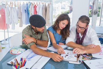 Three fashion designers working in a bright office