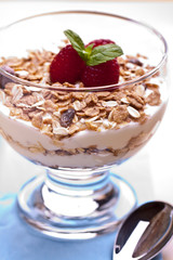 yogurt with muesli and raspberries in small glass