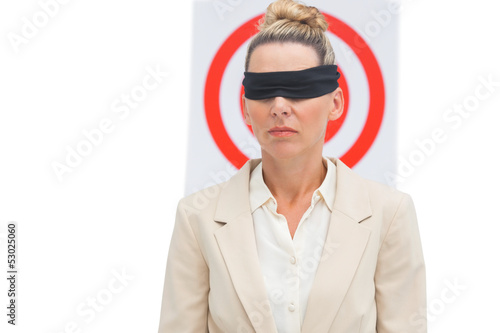 Businesswoman blindfolded in front of target
