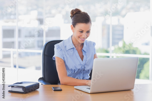 Happy businesswoman working on her laptop