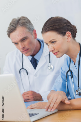 Two doctors focused on a laptop screen