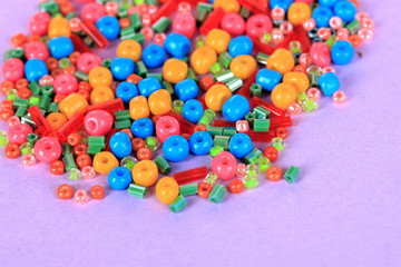 Different colorful beads on purple background