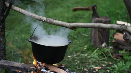 Preparing food in black bonfire pot