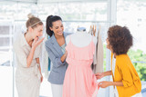 Attractive fashion designers looking at a dress