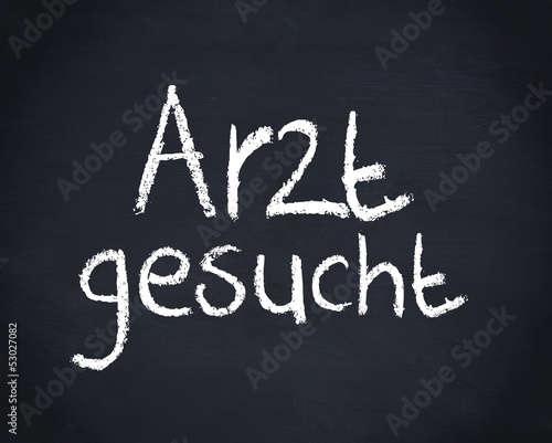 German word arzt gesucht written on a blackboard