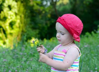 cute little girl sitting in the green field